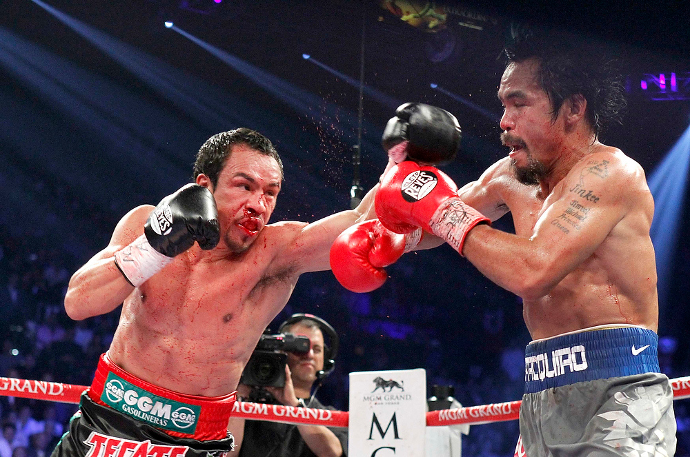 . Juan Manuel Marquez, left, of Mexico punches at Manny Pacquiao of the Philippines during their welterweight fight at the MGM Grand Garden Arena in Las Vegas, Nevada December 8, 2012. REUTERS/Steve Marcus
