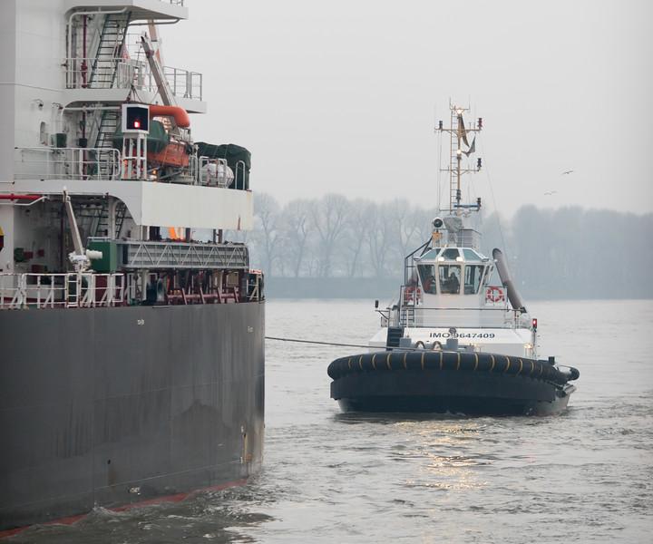 Schlepper an einem Massengutfrachter auf der Elbe in Hamburg