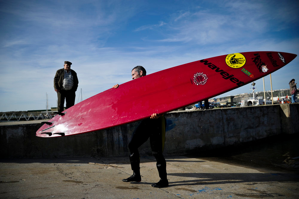 Description of . Hawaiian surfer Garrett McNamara carries his surfboard at Nazare's fishing harbor on January 29, 2013. McNamara arrived on January 28 at Praia do Norte, the