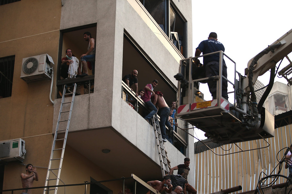 . Lebanese citizens flee their house through a balcony at the site of a car bomb explosion in southern Beirut, Lebanon, Thursday, Aug. 15, 2013. The powerful car bomb ripped through a southern Beirut neighborhood that is a stronghold of the militant group Hezbollah on Thursday, killing people and trapping others in burning buildings, the media said. (AP Photo/Hussein Malla)