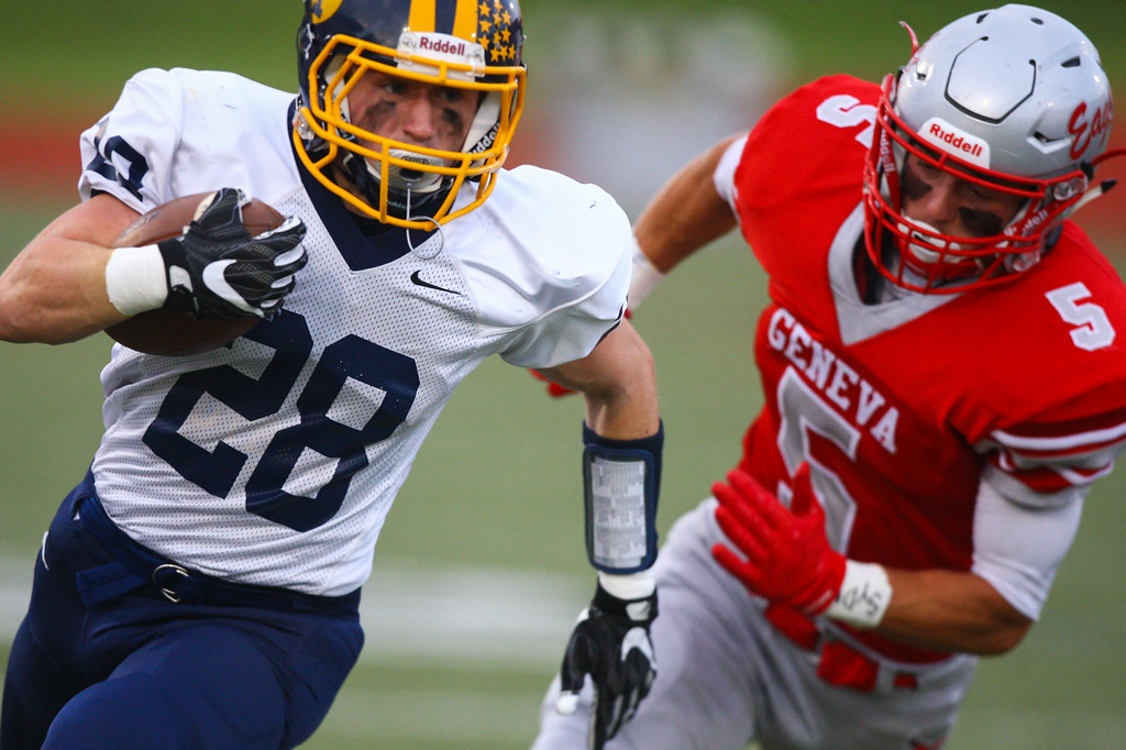 . David Turben - The News-Herald  Kirtland\'s Luke Gardner (28) is pursued by Geneva\'s Blake Peet (5).