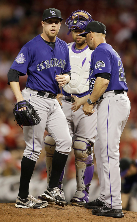 . Colorado Rockies relief pitcher Josh Outman, left, is taken out by manager Walt Weiss, right, in the eighth inning of a baseball game against the Cincinnati Reds, Monday, June 3, 2013, in Cincinnati. Catcher Wilin Rosario watches. Cincinnati won 3-0. (AP Photo/Al Behrman)