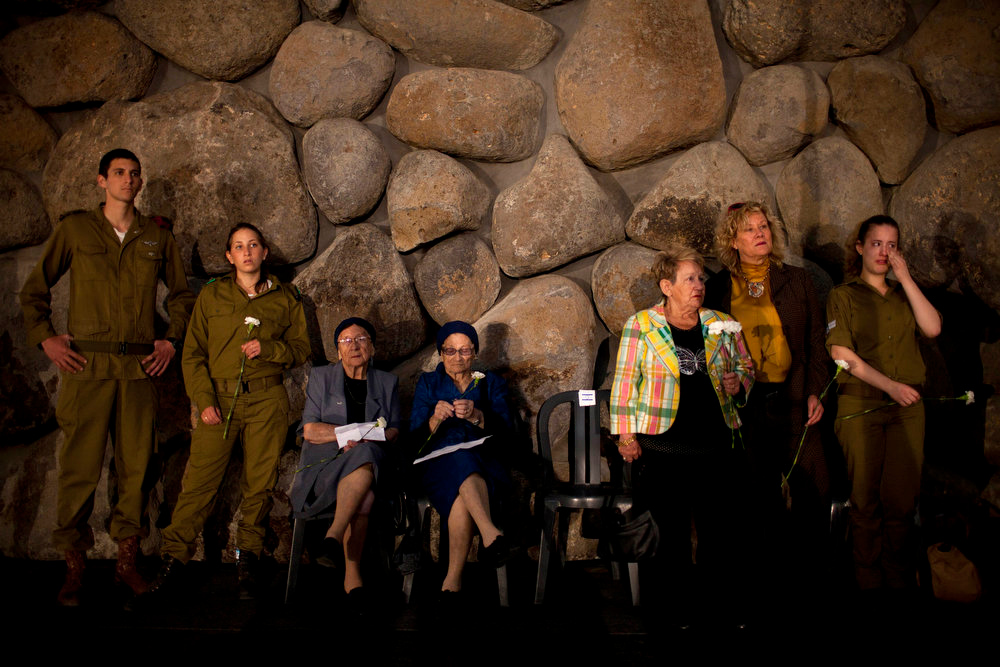 . Holocaust survivors and their relatives hold flowers during a ceremony marking the annual Holocaust Remembrance Day at the Yad Vashem Holocaust Memorial in Jerusalem on Monday, April 8, 2013. Israel came to a standstill for two mournful minutes Monday as sirens pierced the air in an annual ritual to remember the 6 million Jews systematically murdered by German Nazis and their collaborators during the Holocaust in World War II. (AP Photo/Oded Balilty)