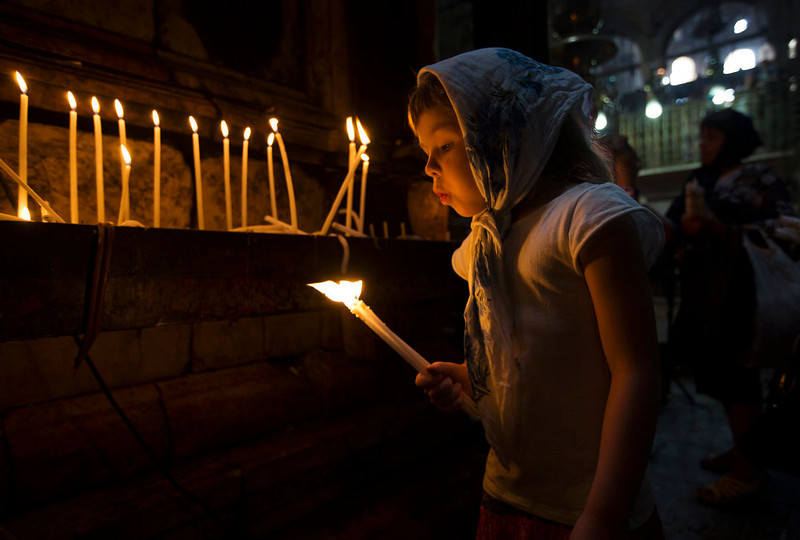 . A Christian girl blows out a candle before the Orthodox Easter service in the Church of the Holy Sepulchre in Jerusalem\'s Old City May 5, 2013. REUTERS/Ronen Zvulun