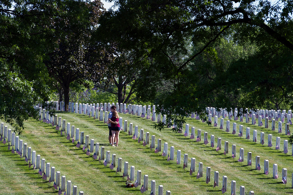. A couple hugs while visiting a grave as embers of the Army 3d U.S. Infantry Regiment, The Old Guard, honor the nation\'s fallen military heroes during its annual Flags In ceremony at Arlington National Cemetery,  Thursday, May 24, 2018, in Arlington, Va. (AP Photo/Cliff Owen)
