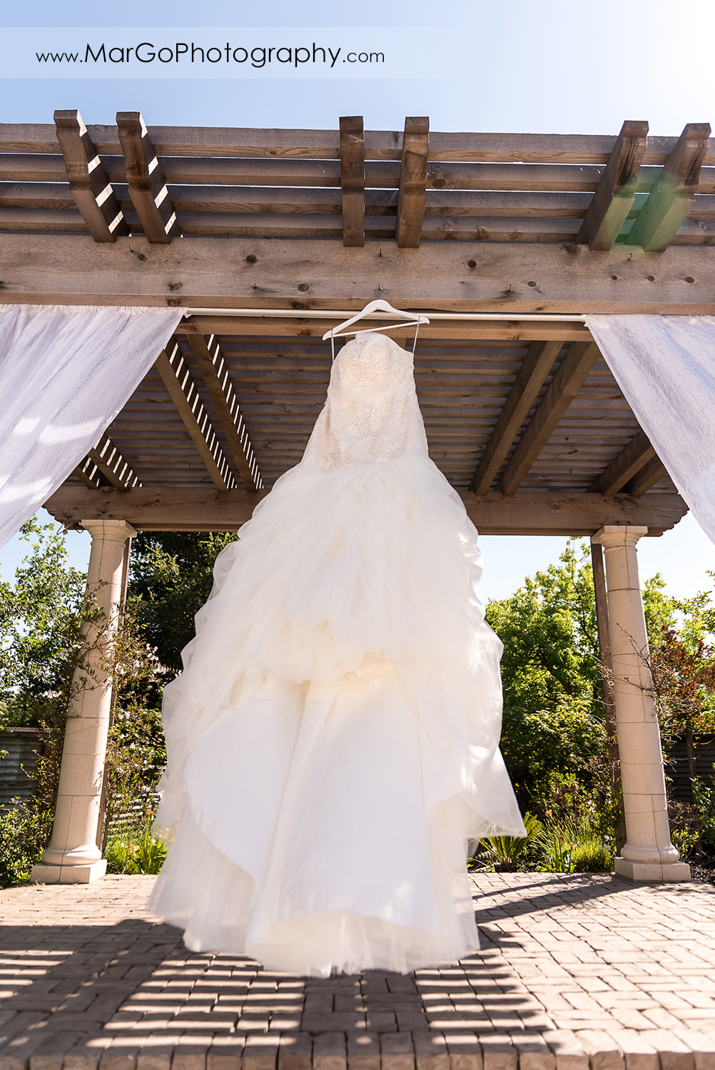 wedding dress hanging on gazebo at Sunol's Casa Bella