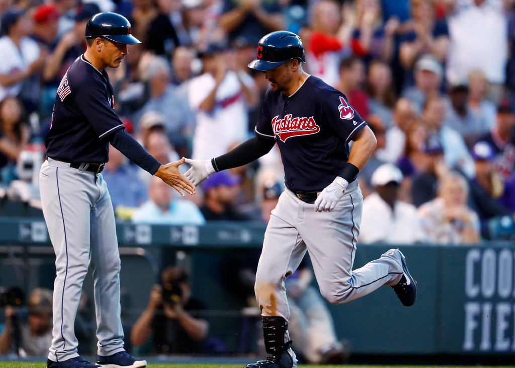 . Cleveland Indians third base coach Mike Sarbaugh, left, congratulates Lonnie Chisenhall as he circles the bases after hitting a solo home run off Colorado Rockies starting pitcher Antonio Senzatela in the fifth inning of an interleague baseball game Tuesday, June 6, 2017, in Denver. The Rockies won 11-3.(AP Photo/David Zalubowski)