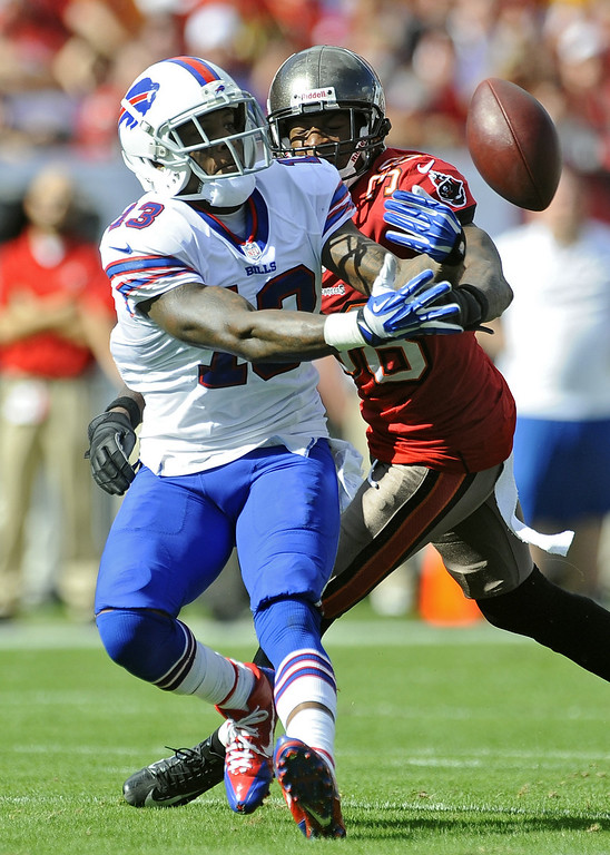 . Buffalo Bills wide receiver Steve Johnson (13) tries to get a hand onto the ball as he is hit by Tampa Bay Buccaneers free safety Dashon Goldson (38) during the second quarter of an NFL football game on Sunday, Dec. 8, 2013, in Tampa, Fla. (AP Photo/Brian Blanco)