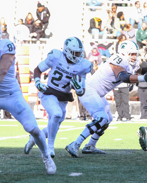 Michigan State RB #27 Weston Bridges breaks through a hole in the line