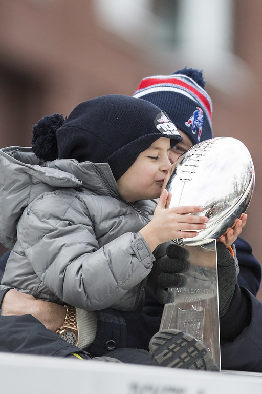 . Benjamin Brady (L) kisses the Lombardi trophy while being held by his dad, Patriots quarterback Tom Brady, on a duck boat during the New England Patriots victory parade on February 4, 2015 in Boston, Massachusetts. (Photo by Scott Eisen/Getty Images)