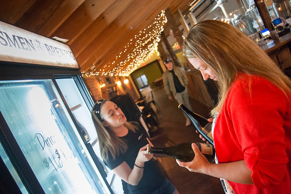 06/25/19 Wesley Bunnell | Staff Jessica Vitale of Kinsmen Brewing, L, helps Sara Cummings with the to go beer selection at the brewery on Tuesday June 25, 2019. Governor Ned Lamont recently signed into law an increase in the amount of beer micro-breweries in Connecticut can sell to a customer from 9 liters to 9 gallons.