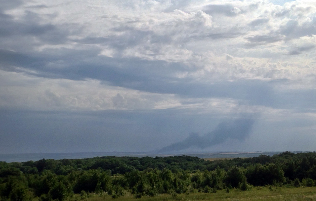 . In this photo taken with a mobile phone provided by Andrei Kashtanov, smoke rises from where a Malaysia Airlines commercial flight plane crashed in eastern Ukraine, Thursday, July 17, 2014. Malaysia Airlines has said 295 people were aboard the flight from Amsterdam to Kuala Lumpur. (AP Photo/Andrei Kashtanov)