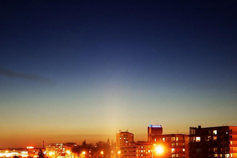 Kometa C2011 L4 panSTARRS nad Olomoucí, 20.3. 2013 19:10. (Rovně vzhůru od věže s modrým neonem.)