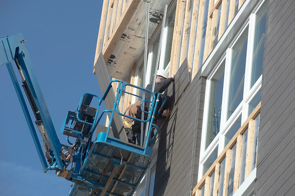 01/02/19 Wesley Bunnell | StaffrrWorkers from Ultimate Construction LLC install siding and trim on the fourth floor of the Columbus Commons building on Thursday afternoon.