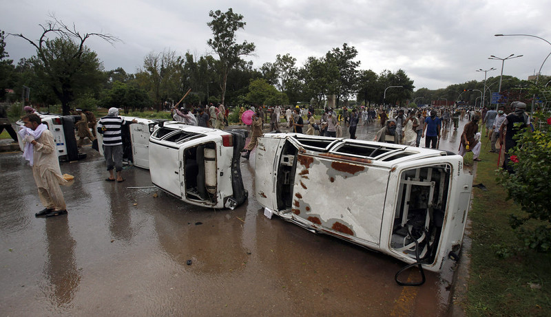 . Pakistani protesters gather next to damaged vehicles during clashes with police in Islamabad, Pakistan on Monday, Sept. 1, 2014. Anti-government protesters and Pakistani police have clashed once again as the demonstrators pushed into a sprawling government complex in the country\'s capital in an effort to try to reach the prime minister\'s official residence. (AP Photo/Anjum Naveed)