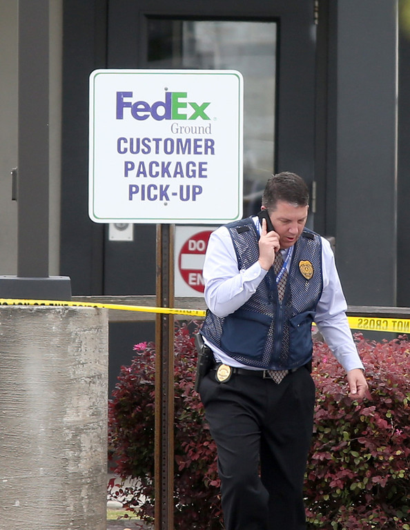 . A law enforcement officer works the scene after an early morning shooting at the Airport Road FedEx facility  Tuesday April 29, 2014, in Kennesaw, Ga.  (AP Photo/Jason Getz)