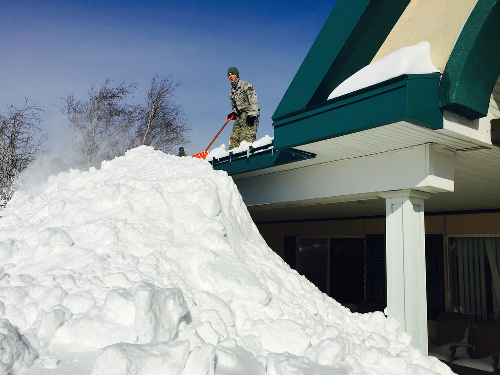 . In this photo taken on Wednesday, Nov. 19, 2014, and released by the New York National Guard, an airman with the New York Air National Guard shovels snow off the roof of the Eden Heights Assisted Living Facility in West Seneca, N.Y.  A new blast of lake-effect snow pounded Buffalo for a third day piling more misery on a city already buried by an epic, deadly snowfall that could leave some areas with nearly 8 feet of snow on the ground when it\'s all done. (AP Photo/New York National Guard, Maj. Mark Frank)