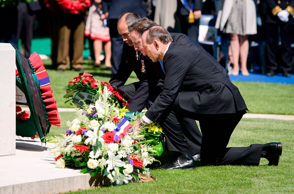 . New Zealand\'s Prime Minister John Key, left, British Prime Minister David Cameron, center, and Australia\'s Prime Minister Tony Abbott, right, lay wreaths during a British D-Day commemoration ceremony at the Bayeux cemetery, northern France, Friday, June 6, 2014. World leaders and veterans gathered by the beaches of Normandy on Friday to mark the 70th anniversary of World War Two\'s D-Day landings. (AP Photo/Leon Neal, Pool)