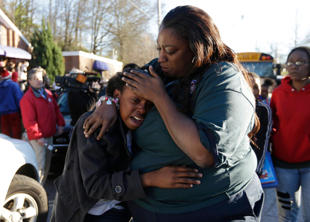 Description of . A woman comforts a child after after a shooting at an Price Middle school in Atlanta Thursday, Jan. 31, 2013. A 14-year-old boy was wounded outside the school Thursday afternoon and a fellow student was in custody as a suspect, authorities said. No other students were hurt. (AP Photo/John Bazemore)