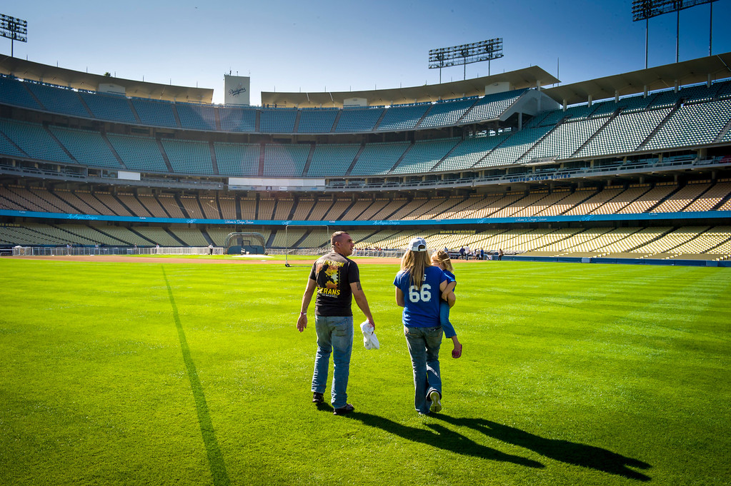 . David Boone of the US Army and his wife Stephanie and daughter Crimson, 3, enter a field of green to participate in Veterans Day at Dodger Stadium Monday, November 11, 2013.  The dodgers hosted 100 active duty and retired military to Dodger Stadium to take part in batting practice, enjoy and Dodger lunch and tour the facilities.    ( Photo by David Crane/Los Angeles Daily News )
