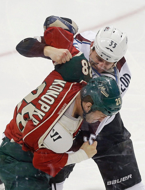 . Colorado Avalanche\'s Cody McLeod, top, and Minnesota Wild\'s Zenon Konopka fight during the first period of an NHL hockey game Thursday, March 14, 2013, in St. Paul, Minn. Both received five-minute fighting penalties. (AP Photo/Jim Mone)