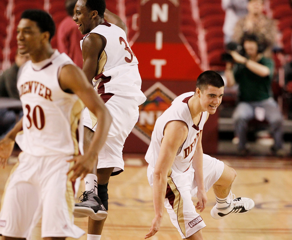 . Denver guard Cam Griffin, front, joins forward Chris Udofia, back left, and guard Brett Olson in celebrating after Denver\'s 61-57 victory over Ohio in a first-round NIT college basketball game in Denver on Tuesday, March 19, 2013. (AP Photo/David Zalubowski)