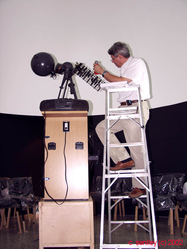 """""""Al:  Just wanted you to see how similar your planetarium projector is to our Goto's.  Standing on the ladder, I'm calibrating the instrument and planetary positions with  ephemeris information, to begin working with the public at the museum.""""  """"If your planetarium has anything like a program card then it is more fit for a public show  than ours. We have to do everything manually and according to """"pre-learned"""" steps and  sequences. The intro of the recorded show has some cool electronic minutes or so  of getting the mood until the sun appears. Then we simulate sunset, the red dawn effect,  the apparition of the first stars, but we keep the skyglow lightly illuminated until we talk  about dark skies where everything goes pitch black and the wows start to be heard when  about maybe 700 stars appear to about mag 4. The whole thing lasts about 28 minutes  and eventually ends up with Holst's The Planet's music for each planet described and  proyected with the slide machine. A didactic teaching machine converted into a show  where nobody complains of gets bored is to us a great accomplishment!  -  Eric Ramos"""""""