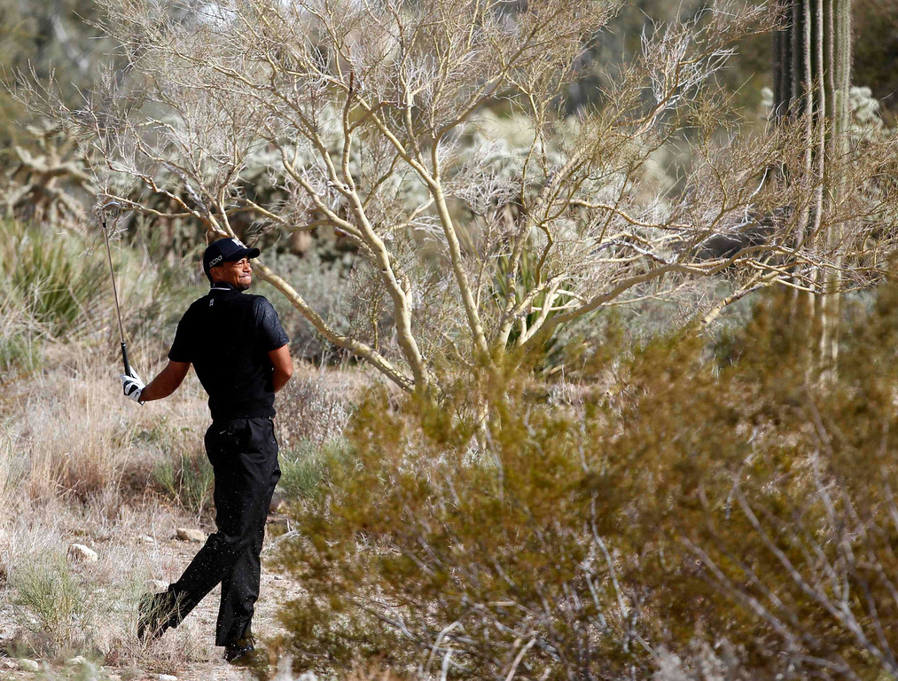 . Tiger Woods of the U.S. hits from the rough on the second hole against his compatriot Charles Howell III during the weather delayed first round of the WGC-Accenture Match Play Championship golf tournament in Marana, Arizona February 21, 2013. REUTERS/Matt Sullivan