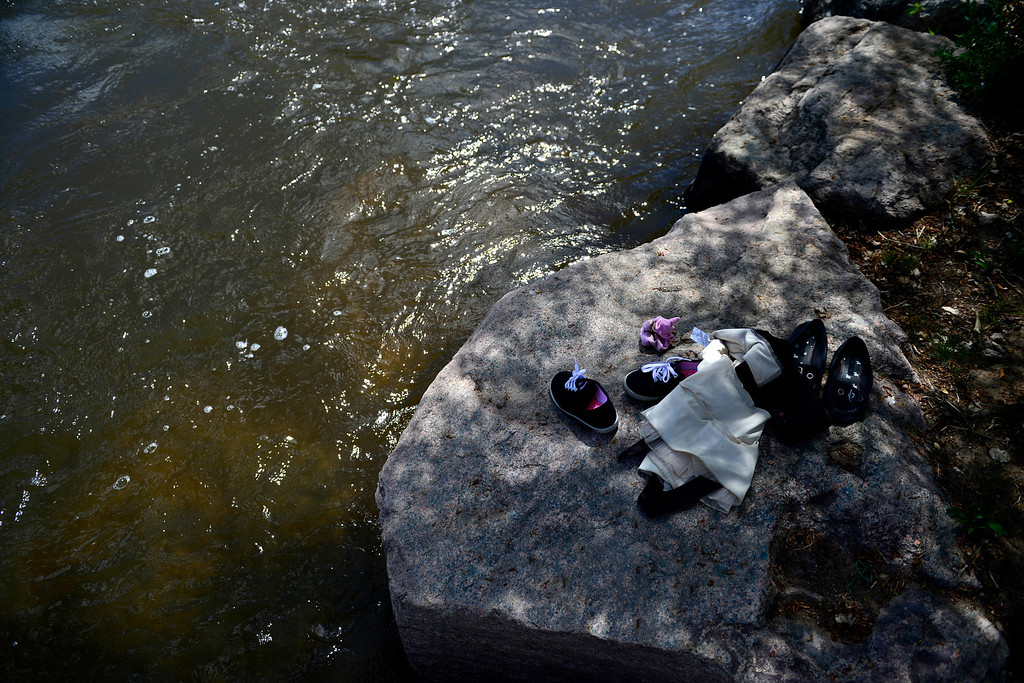 . People leave their belongings on dry land as they get into the water during Golden Games at the Clear Creek Whitewater Park. (Photo by AAron Ontiveroz/The Denver Post)