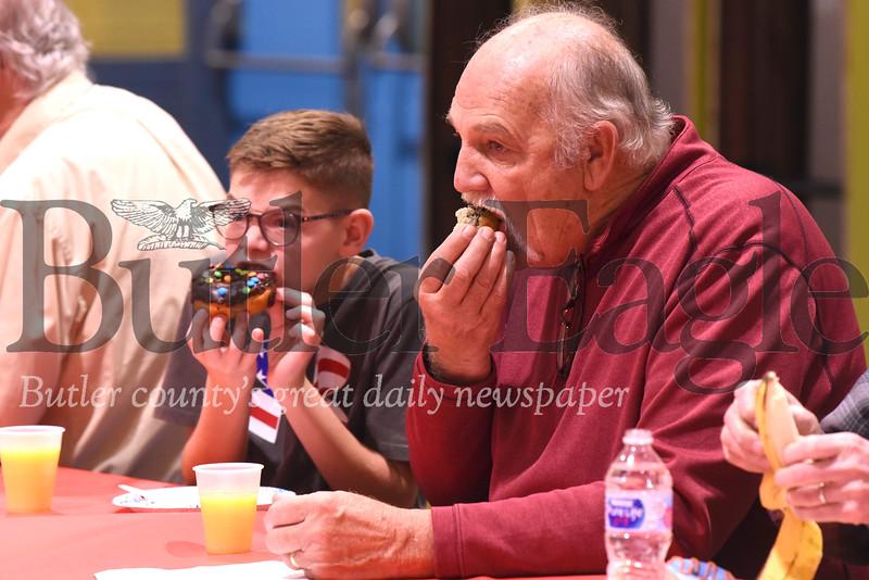 U.S. Army veteran Jim Brown and his step grandson Grady Robb enjoy donuts at the South Butler Intermediate Elementary School veterans breakfast Friday. Seb Foltz/Butler Eagle