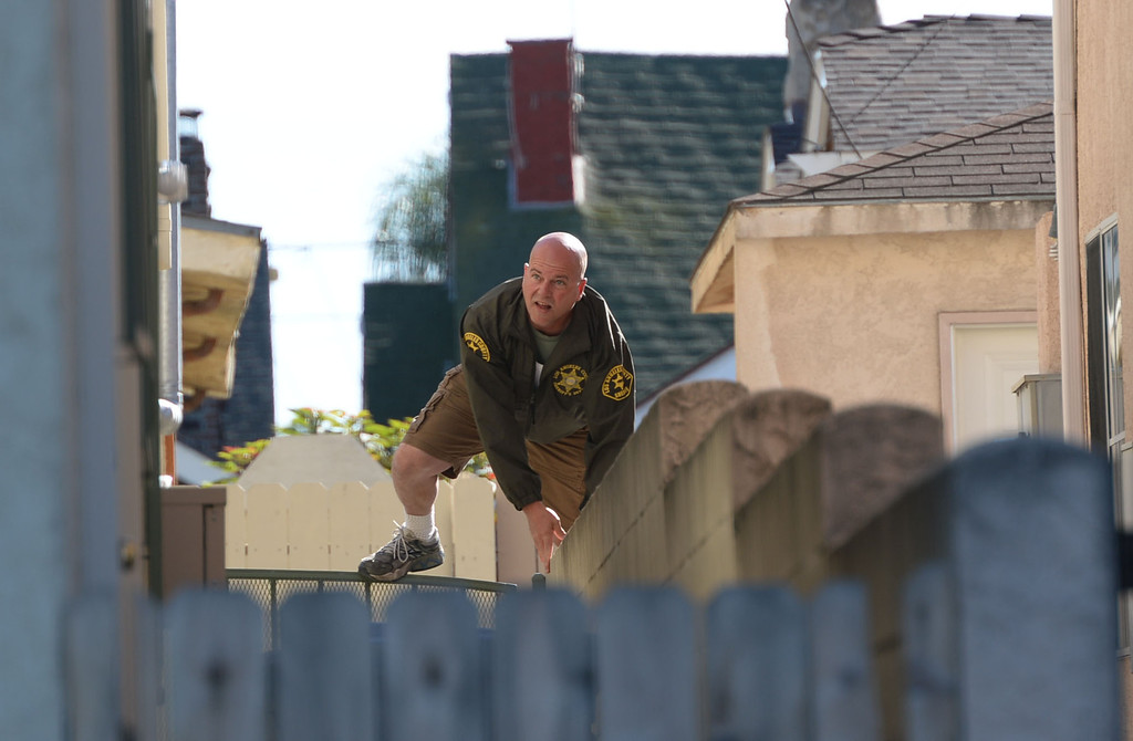 . A man in handcuffs eluded Sheriff\'s deputies before finally being caught hiding in a trash can in the alley behind the 700 block of 10th Street in San Pedro Wednesday, December 03, 2013.  A deputy hops a fence in the location of where the suspect was caught. Photo by Steve McCrank/DailyBreeze