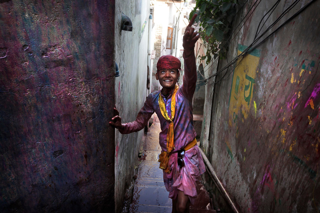 . A young villager from Nandgaon soaked in water and colors arrives in Barsana village during the Lathmar Holy festival, the legendary hometown of Radha, consort of Hindu God Krishna, in Barsana, 115 kilometers (71 miles) from New Delhi, India, Thursday, March 21, 2013. During Lathmar Holi the women of Barsana beat the men from Nandgaon, the hometown of Krishna, with wooden sticks in response to their teasing as they depart the town. (AP Photo/Manish Swarup)