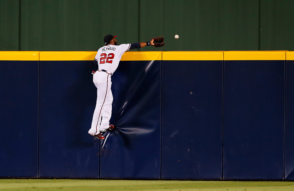 . ATLANTA, GA - OCTOBER 03: Jason Heyward #22 of the Atlanta Braves tries to catch a homerun hit by Adrian Gonzalez #23 of the Los Angeles Dodgers in the third inning during Game One of the National League Division Series at Turner Field on October 3, 2013 in Atlanta, Georgia.  (Photo by Kevin C. Cox/Getty Images)
