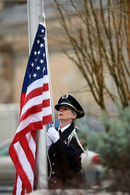 . A Colorado Department of Corrections Honor Guard member, raises the American flag to half-staff at the beginning of the Colorado Department of Corrections Fallen Officer Memorial honoring the head of the DOC, Tom Clements, at the Territorial Correctional Facility park Saturday morning, March 15, 2014.   (Photo By Andy Cross / The Denver Post)