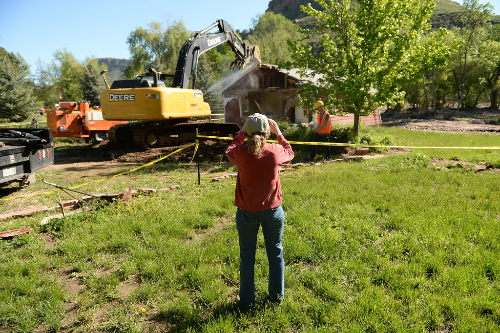 . Home owner Vicki Rivers takes photos of her home as crews, with Ecoos Environmental and Disaster Restoration, work on demolishing a home in Lyons that was damaged by last years flood, May 27, 2014. (Photo by RJ Sangosti/The Denver Post)