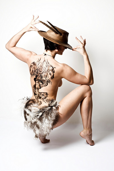 This lady is a fire performer, hence the firebird which is protected by her lioness guardians. The cheetah is her totem animal and the top hat symbolizes her being a performer.
