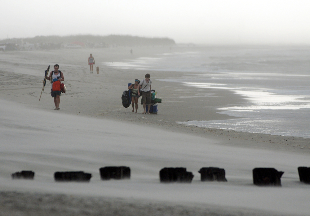 . Clouds and rains move in as beachgoers leave Freeman Park at the north end of Carolina Beach, N.C., Thursday, July 3, 2014. Residents along the coast of North Carolina are bracing for the arrival of the Hurricane Arthur, which threatens to give the state a glancing blow on Independence Day. (AP Photo/Wilmington Star-News, Mike Spencer)