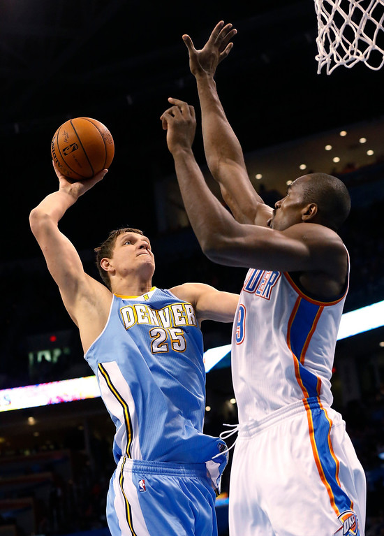. Denver Nuggets center Timofey Mozqov (25) shoots in front of Oklahoma City Thunder forward Serge Ibaka (9) in the first quarter of an NBA basketball game in Oklahoma City, Monday, March 24, 2014. (AP Photo/Sue Ogrocki)