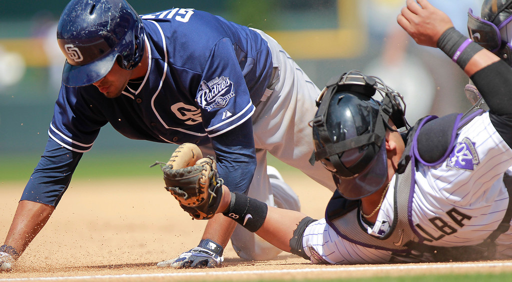 . Colorado Rockies catcher Yorvit Torrealba, right, tags out San Diego Padres\' Jesus Guzman, after  tagging out Jedd Gyorko for an unassisted double play during the sixth inning of a baseball game Wednesday, Aug. 14, 2013 in Denver. (AP Photo/Barry Gutierrez)