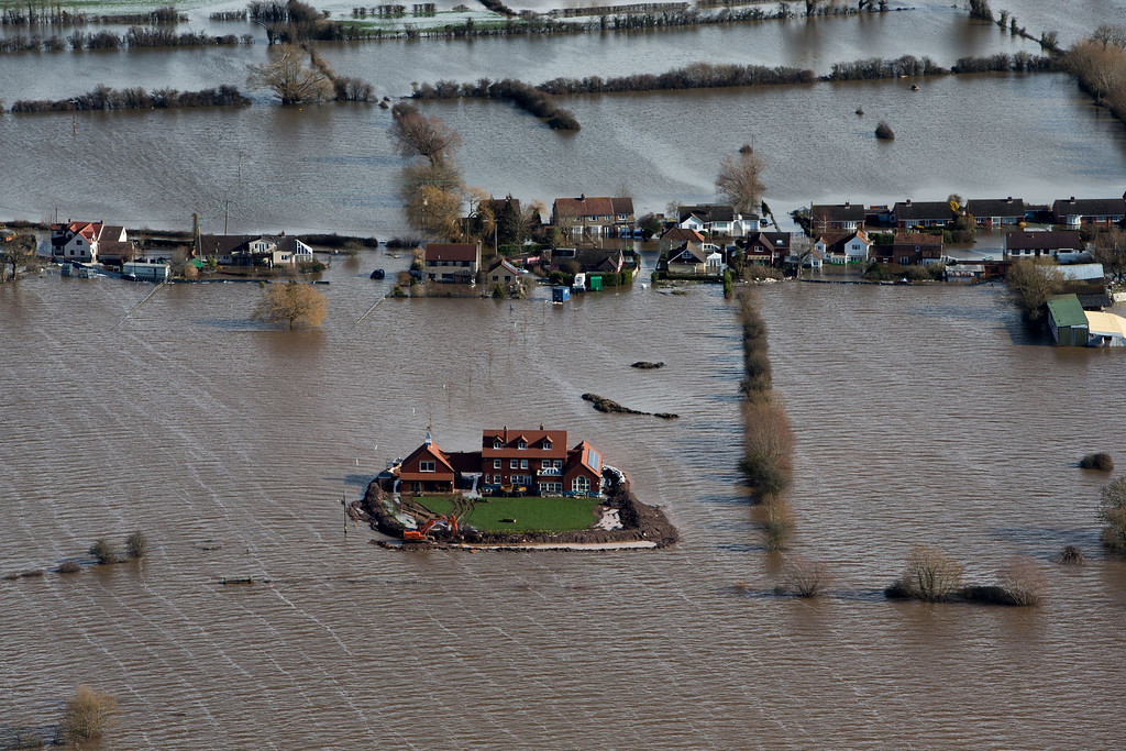 . Flood waters inundate the area as one house stands alone and dry near the flooded village of Moorland in Somerset, southwest England, Thursday Feb. 13, 2014.  The house is owned by Sam Notaro, who has built his own levee to hold back the flood waters, as the local communities face further misery in the coming days with heavy rain, wind and snow predicted to sweep across Britain. (AP Photo/Steve Parsons, PA)