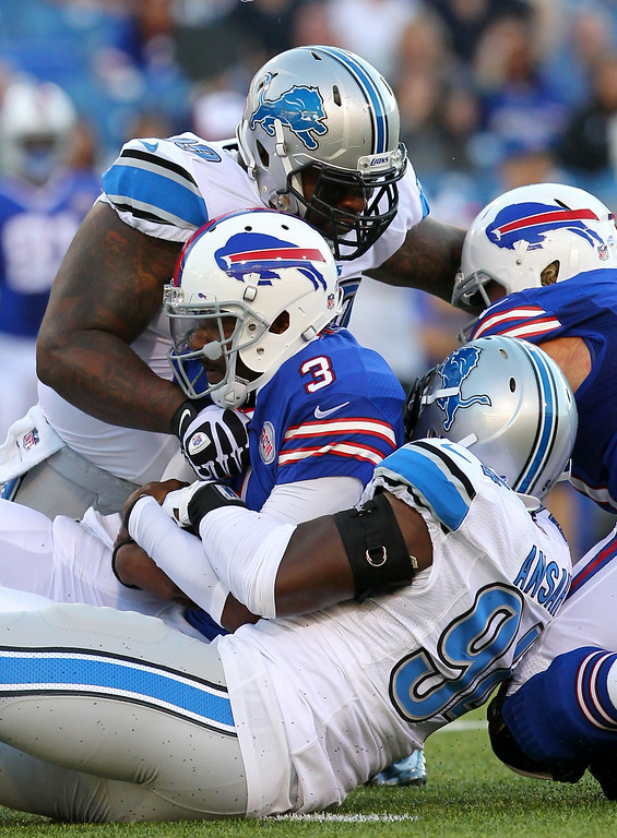 . Buffalo Bills quarterback EJ Manuel (3) is brought down by Detroit Lions defensive end Ezekiel Ansah (94) and defensive tackle C.J. Mosley (99) during the first half of a preseason NFL football game, Thursday, Aug. 28, 2014, in Orchard Park, N.Y. (AP Photo/Bill Wippert)