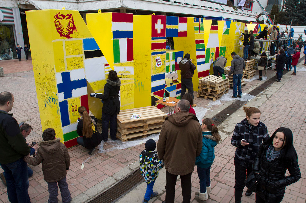 ". Kosovo Albanian volunteers gather to paint the flags of the countries that have recognized Kosovo\'s independence on to the ""NEWBORN\"" monument marking the secession of Kosovo from Serbia in capital Pristina on Saturday, Feb. 16, 2013. (AP Photo / Visar Kryeziu )"