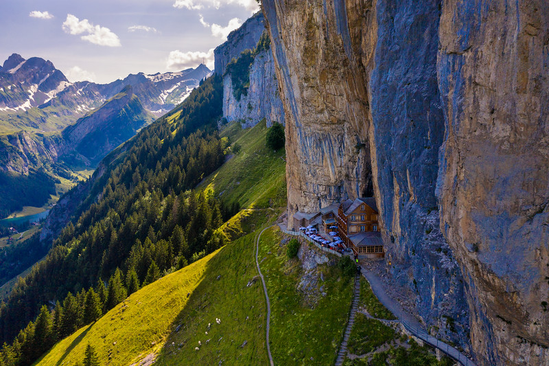 Swiss Alps and a restaurant under a cliff on mountain Ebenalp in Switzerland