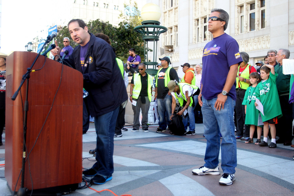 . John Arantes, left, president of SEIU Chapter 1021, speaks as vice president Saul Almanza looks on during a rally in support of BART workers at Frank Ogawa Plaza in Oakland, Calif., on Thursday, Aug. 1, 2013. (Ray Chavez/Bay Area News Group)