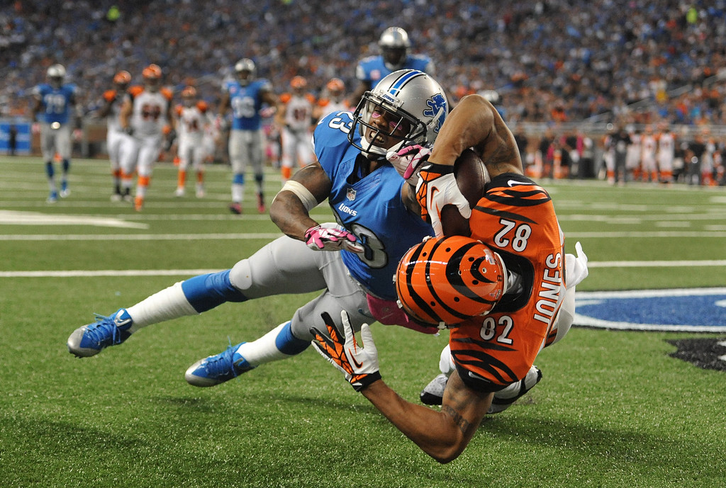 . Cincinnati Bengals wide receiver Marvin Jones (82) catches a 12-yard touchdown reception as Detroit Lions cornerback Chris Houston (23) defends in the second quarter of an NFL football game against Sunday, Oct. 20, 2013, in Detroit. (AP Photo/Jose Juarez)
