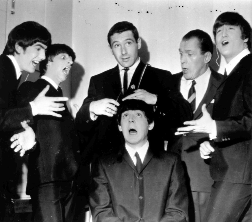 . American speed skating champion Terry McDermott, top centre,a barber by trade, prepares to take a swipe at the famed locks of Beatle Paul McCartney, seated , to the mock horror of the other Beatles and TV host Ed Sullivan, during rehearsals at the TV Studio, New York, Feb. 9, 1964. From left, George Harrison, Ringo Starr, McDermott, Ed Sullivan and John Lennon. (AP Photo)