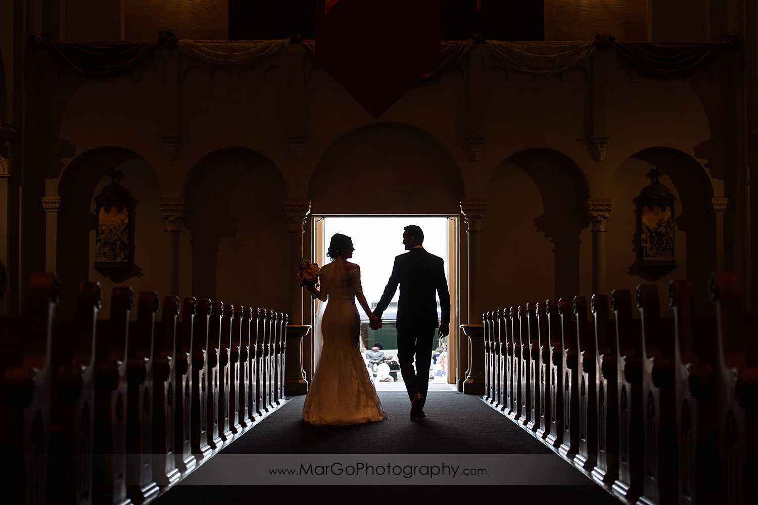 silhouette of bride and groom walking down the aisle after wedding ceremony at Oakland Church of Saint Leo the Great