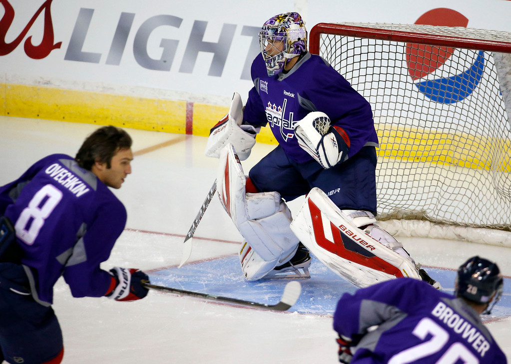 . Washington Capitals goalie Justin Peters (35), left wing Alex Ovechkin (8), from Russia, and right wing Troy Brouwer (20) wear purple jerseys during warm ups to promote cancer awareness, before an NHL hockey game against the Detroit Red Wings, Wednesday, Oct. 29, 2014, in Washington. (AP Photo/Alex Brandon)