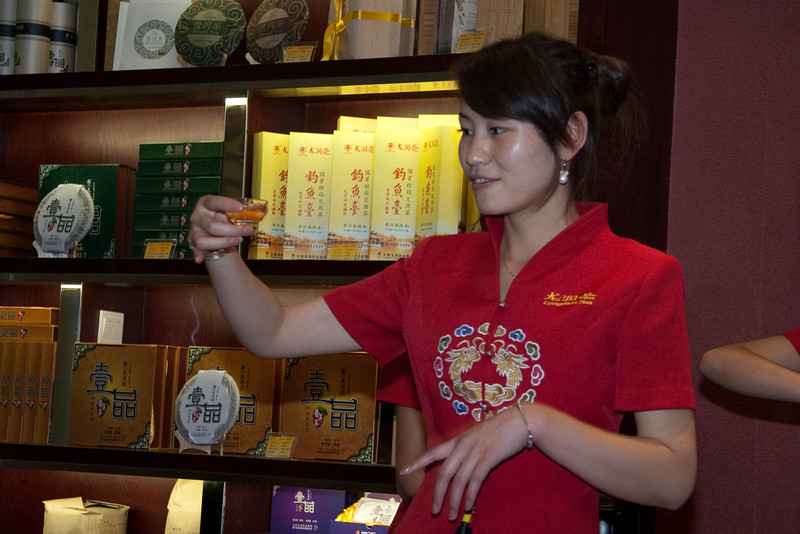 Sales lady showing us the proper way to drink tea.