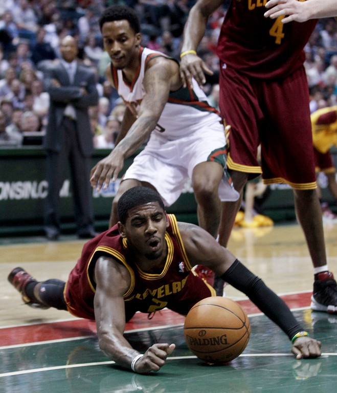 . Cleveland Cavaliers\' Kyrie Irving dives after a loose ball in front of Milwaukee Bucks\' Brandon Jennings during the first half of an NBA basketball game Wednesday, March 14, 2012, in Milwaukee. (AP Photo/Morry Gash)